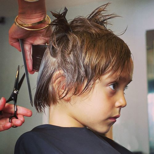 Cropped hand of woman cutting hair of boy