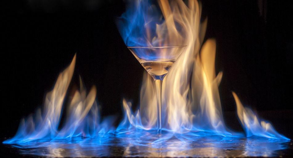 Close-up of lit martini glass against black background