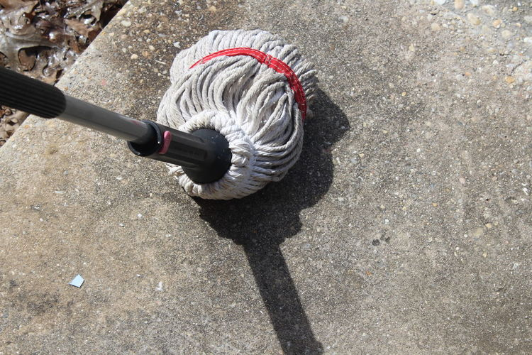 High angle view of mop on footpath during sunny day