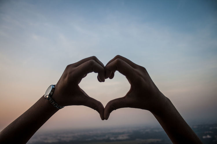 Cropped image of hands making heart shape against cloudy sky