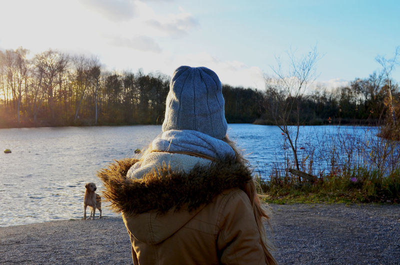 Rear view of man with dog on lake against sky