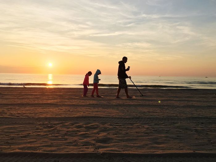 Family Walking On Beach During Sunset