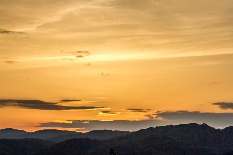Scenic View Of Mountains Against Orange Sky During Sunset