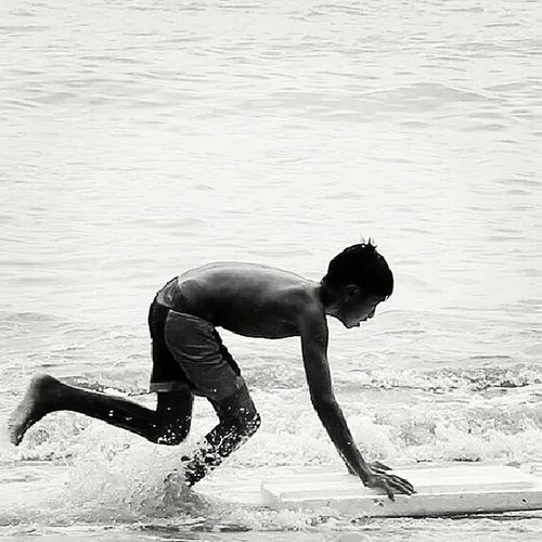 a kid surfing on the beach using the styro lid of an ice box.. :)) Realquezon Snapshot Canon Kemengphotography Summer2014 Beach Surfing Summersapinas Itsmorefuninthephilippines ;) Nature's Diversities The Great Outdoors - 2016 EyeEm Awards The Great Outdoors With Adobe The Following Fresh On Eyeem  People Of The Oceans Feel The Journey Original Experiences Eyeem Philippines Adventure Club