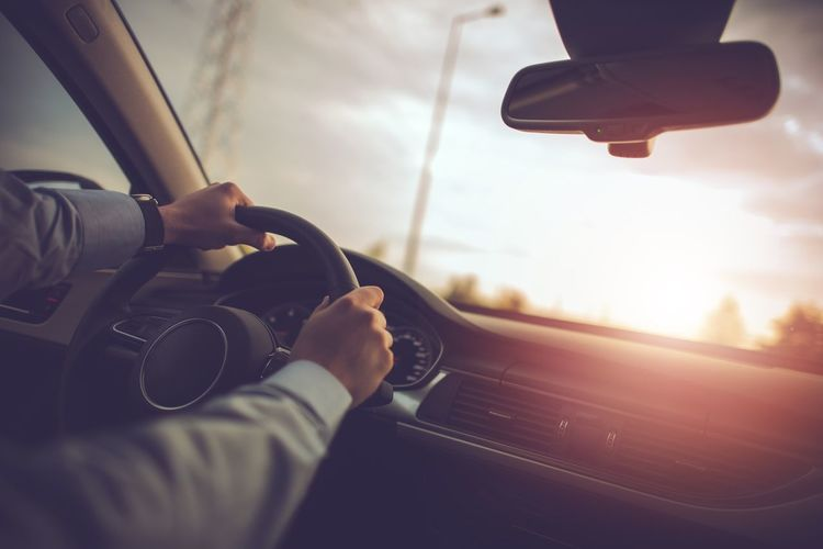 Cropped image of man driving car against sky