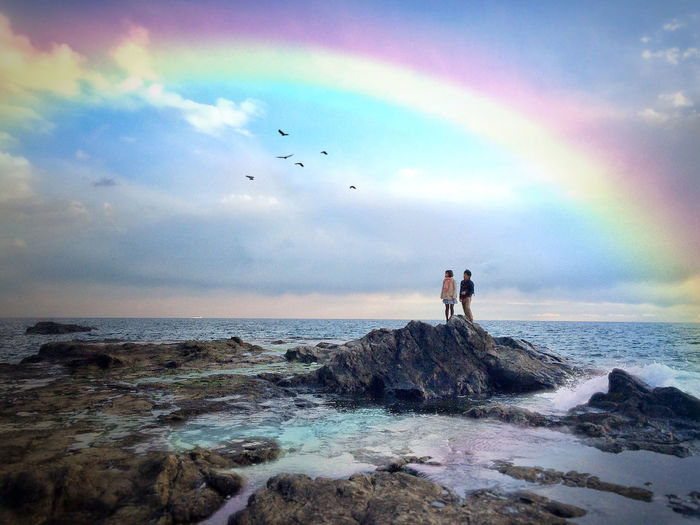Man and woman standing on top of rock amidst sea looking at rainbow