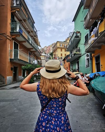 Rear view of woman standing on street against buildings