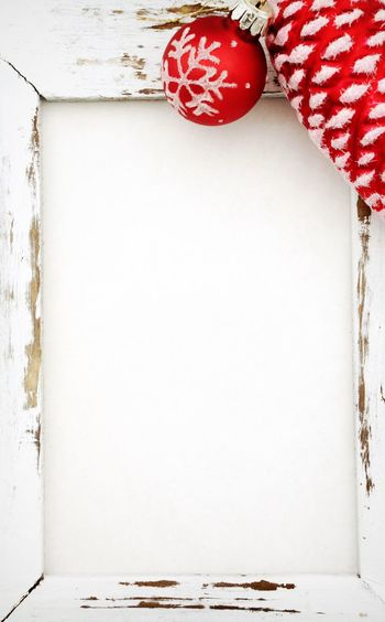 Full frame shot of white wooden door with red bauble