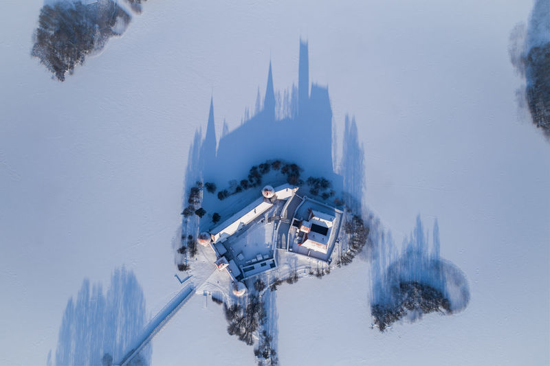 Aerial view of houses amidst snow covered landscape during winter