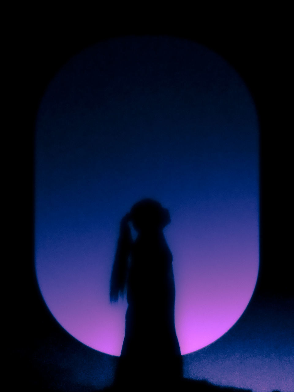 REAR VIEW OF SILHOUETTE WOMAN STANDING AGAINST DARK SKY