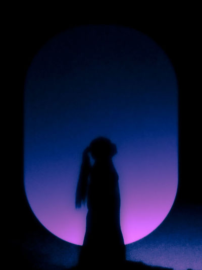 Rear view of silhouette woman standing against blue sky