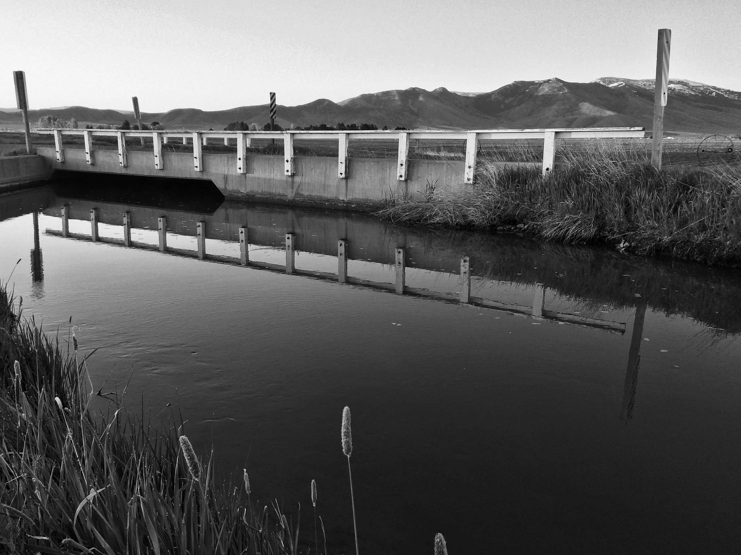 water, built structure, clear sky, architecture, river, bridge - man made structure, railing, lake, reflection, tranquility, connection, nature, tranquil scene, pier, outdoors, no people, grass, day, bridge, scenics