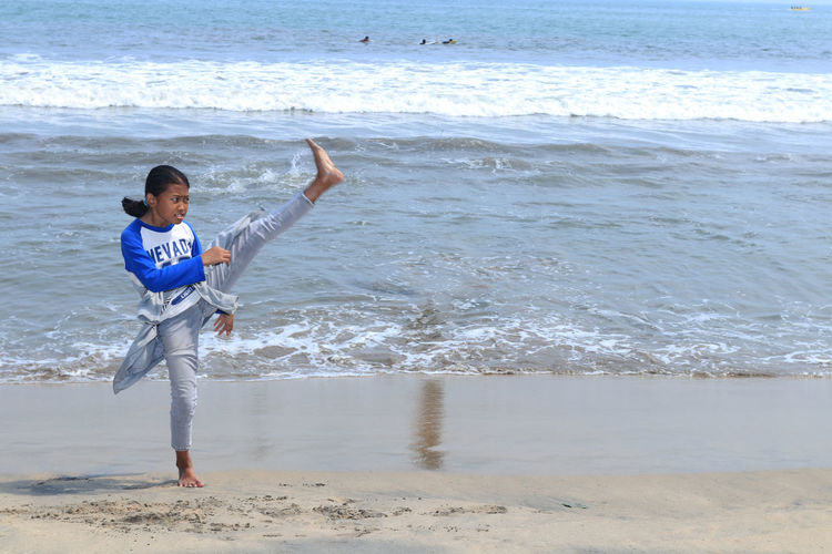 Full Length Of Girl Doing Martial Arts At Beach
