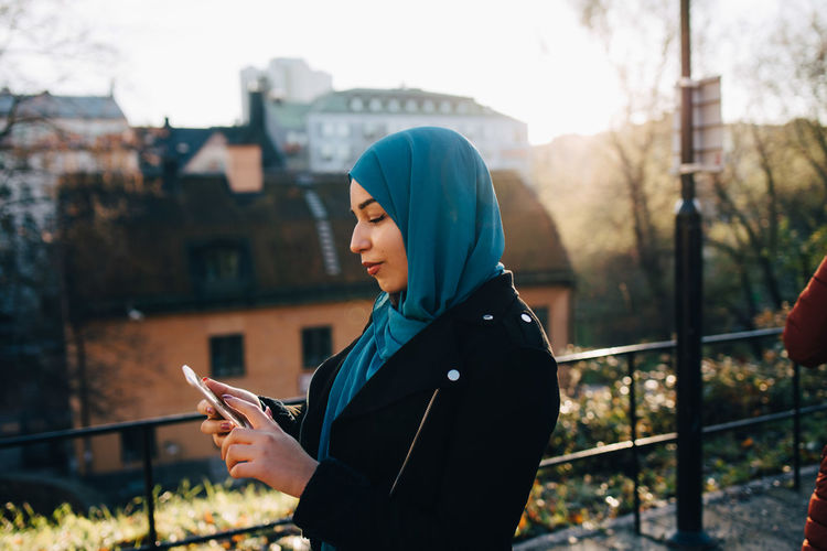 Side view of young woman using mobile phone in city