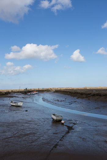 Boats moored in Morston Creek, Norfolk, England at low tide Copy Space Creek Beach Beauty In Nature Blue Cloud - Sky Day Land Low Tide Mode Of Transportation Moored Mud Nature Nautical Vessel No People Non-urban Scene Outdoors Rowboat Scenics - Nature Sea Sky Tranquil Scene Tranquility Transportation Water