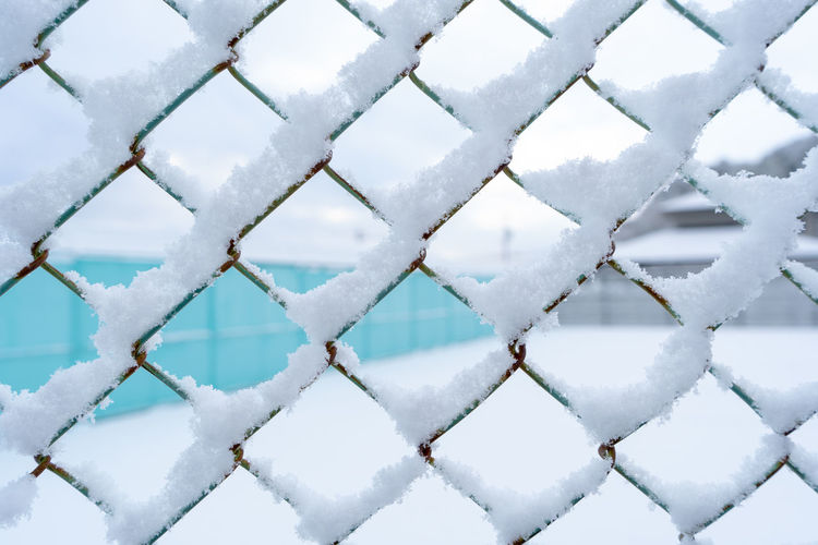 Full frame shot of snow covered fence during winter