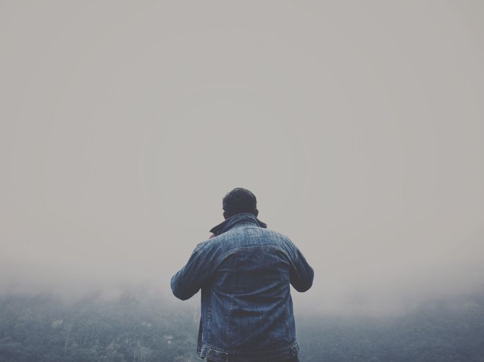 Rear view of man standing against sky during foggy weather