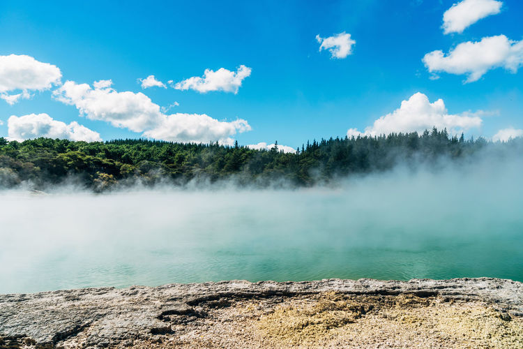 Scenic view of geyser against blue sky