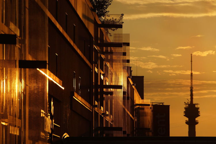 Low angle view of illuminated buildings against sky during sunset