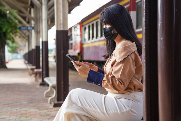 Side view of woman wearing flu mask using mobile phone at railroad station