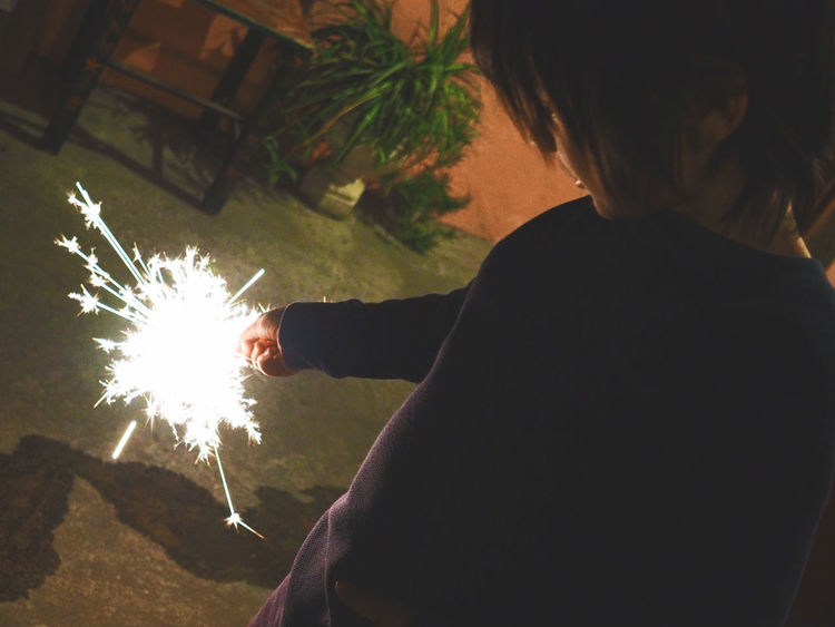 Celebrating the New Year Adult Adults Only Boy Child Firework - Man Made Object Holding Human Body Part Human Hand Illuminated Indoors  Leisure Activity Lifestyles Men New Year New Year's Eve Fireworks Night One Person People Real People Rear View Sparkler Sparks Tree Wireless Technology
