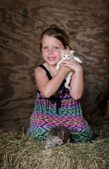 a young girl holds new kittens as she sits on a bale of straw Kittens Animal Themes Cats Childhood Cute Domestic Animals Family Farm Friendship Full Length Happiness Indoors  Looking At Camera Mammal One Animal One Person People Pet Pets Real People Smiling Straw Young Girl