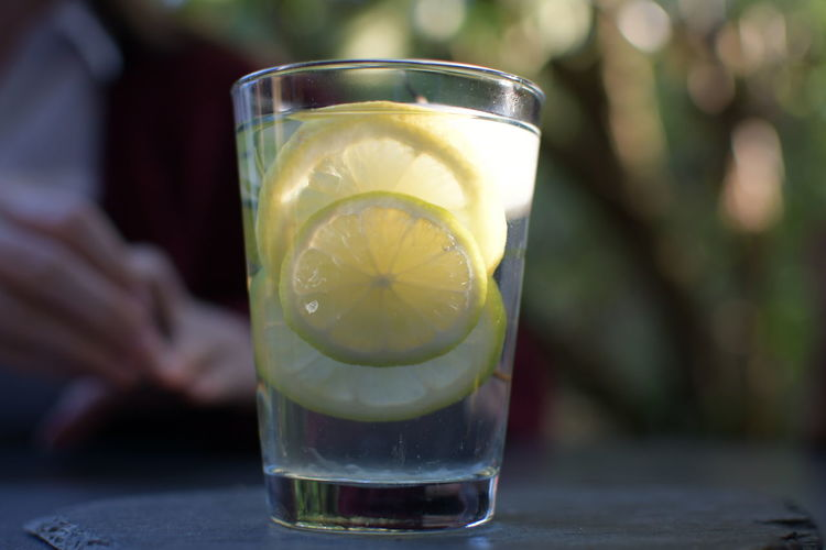 Close-up of lemon slices and drink in drinking glass on table outdoors