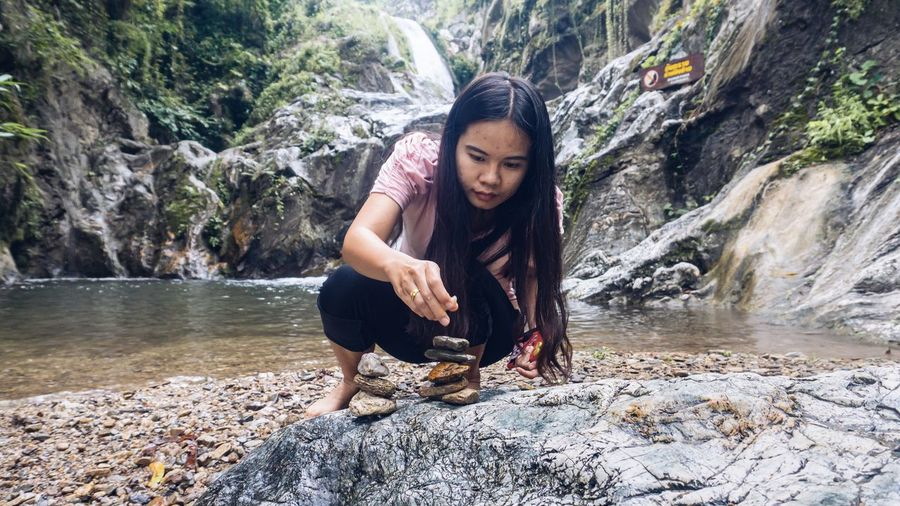 Young woman stacking stones by river at forest