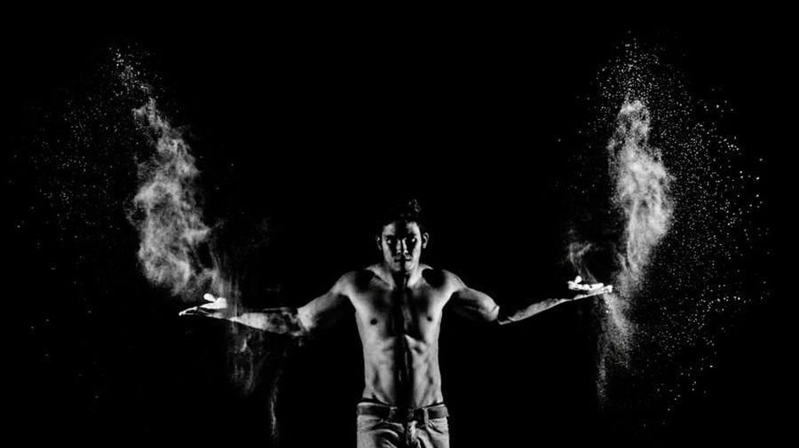 Full length of shirtless man against black background