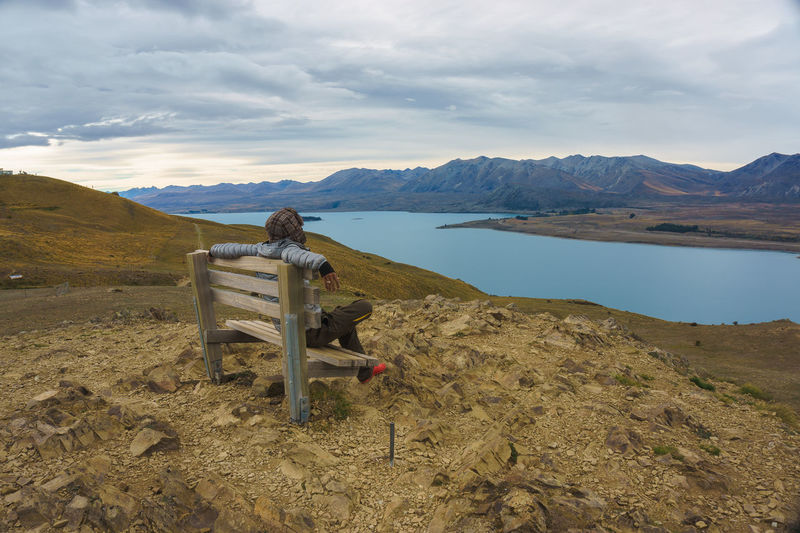 Man sitting on bench at mountain against sky