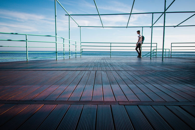 Full length of man standing by sea on pier