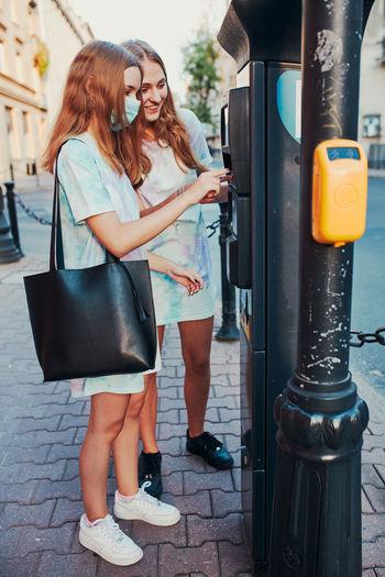 Full length of girls standing on street in city