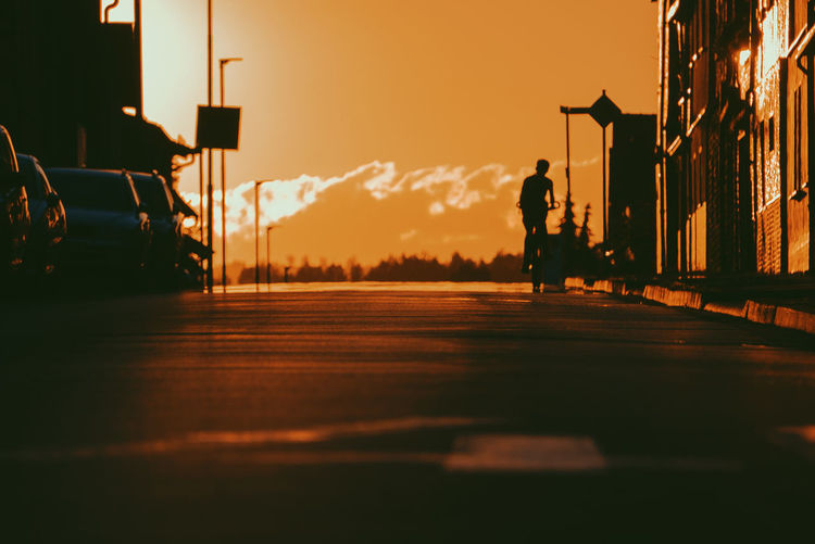 Silhouette man standing on street against sky during sunset