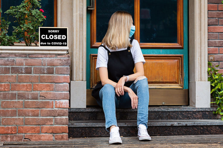 Caucasian waitress woman wearing medical mask and sorry we're closed. coronavirus covid-19 pandemic
