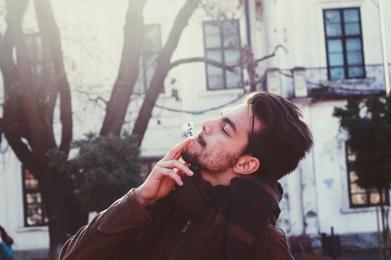 Enjoy The New Normal Beard One Person Only Men Headshot One Man Only Lifestyles Young Adult Adults Only Leisure Activity City Warm Clothing Outdoors Tree Adult People Portrait Men Eyeglasses  Day Smoking Smoke EyeEm Best Shots Eye4photography