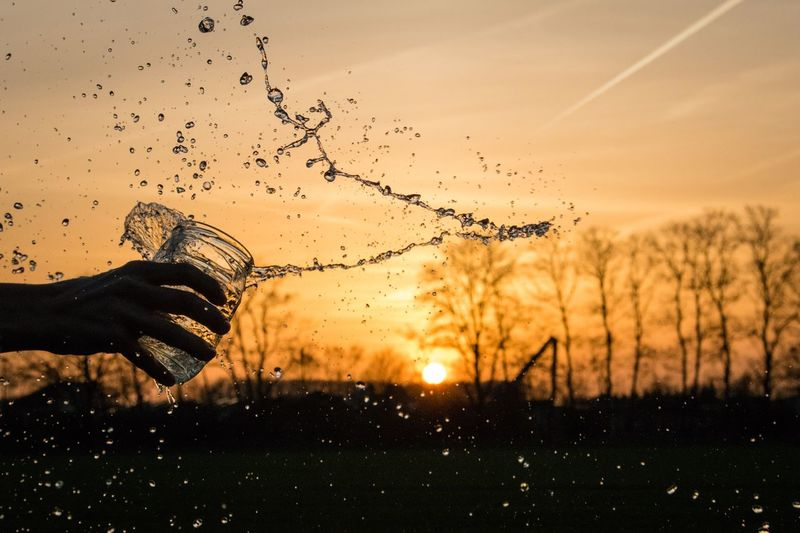 Cropped hand splashing water against sky during sunset