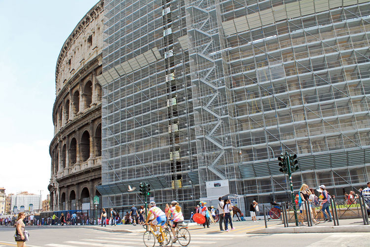 People Walking On Street Against Coliseum
