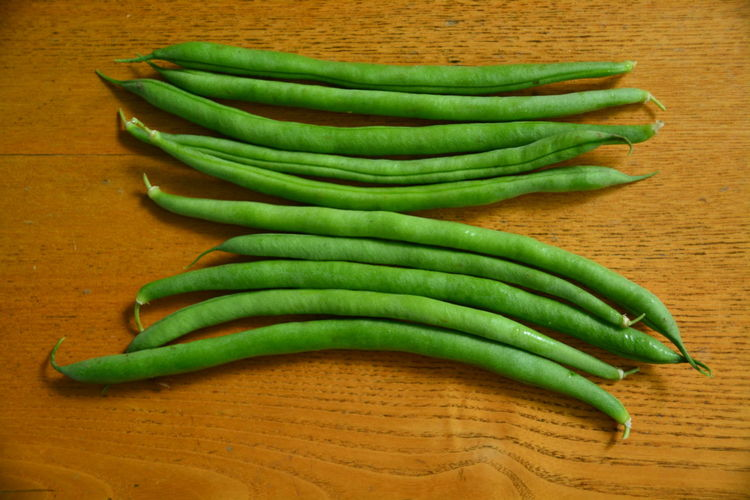 High angle view of green beans on wooden table
