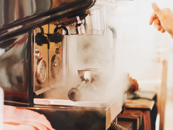 Cropped hand of person by steam emitting from espresso maker at cafe