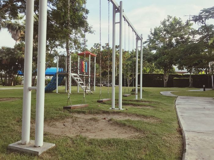 Plant Tree Grass Park Park - Man Made Space Day Nature Swing Outdoors Built Structure No People Green Color Fence Growth Architecture Boundary Playground Outdoor Play Equipment Sky