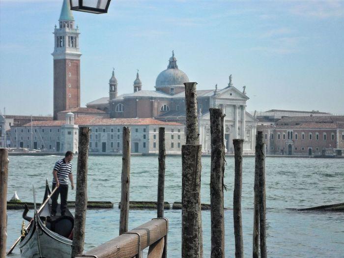 Gondolier standing on boat in grand canal against church of san giorgio maggiore