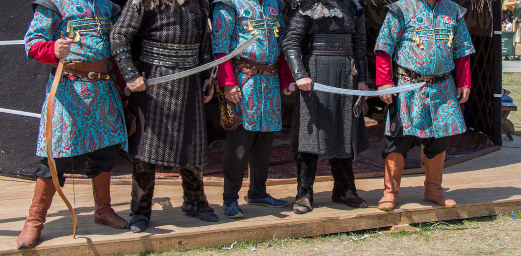 Low section of people in costume with weapon standing outdoors