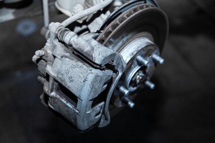 Close-up of a car hub, brake caliper, brake pads, brake disc, wheel bearing prepared for repair.