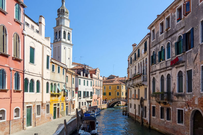 Gondolas moored on grand canal amidst buildings