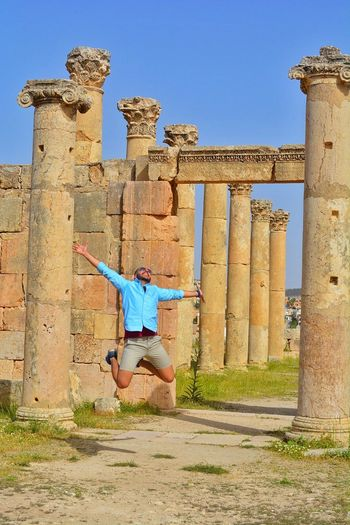 Man jumping against ancient old ruin columns
