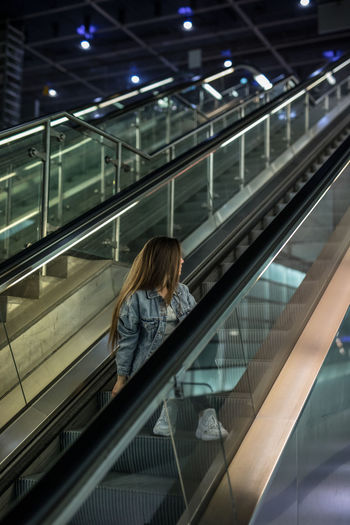 Full length of woman looking away while sitting on escalator
