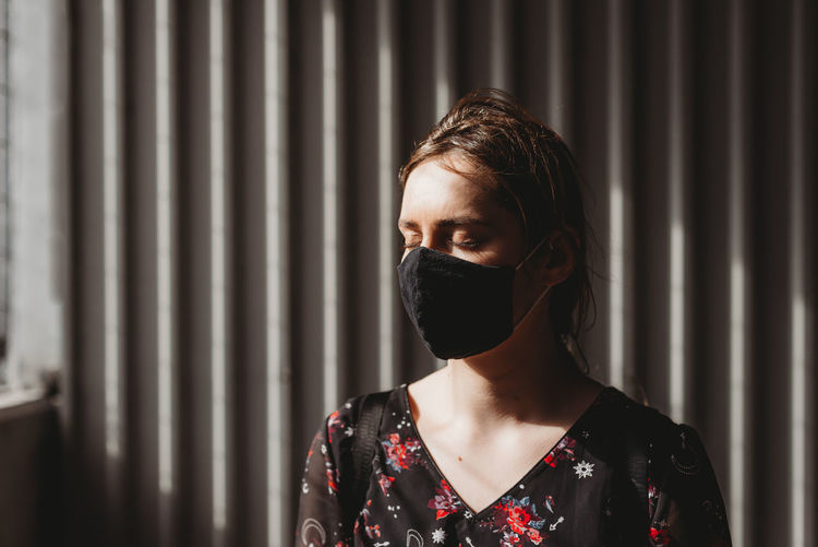 Depressed woman with face mask closed eyes on the sun