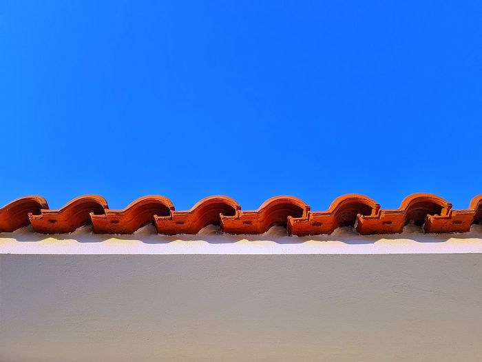 Low angle view of roof tiles against clear blue sky