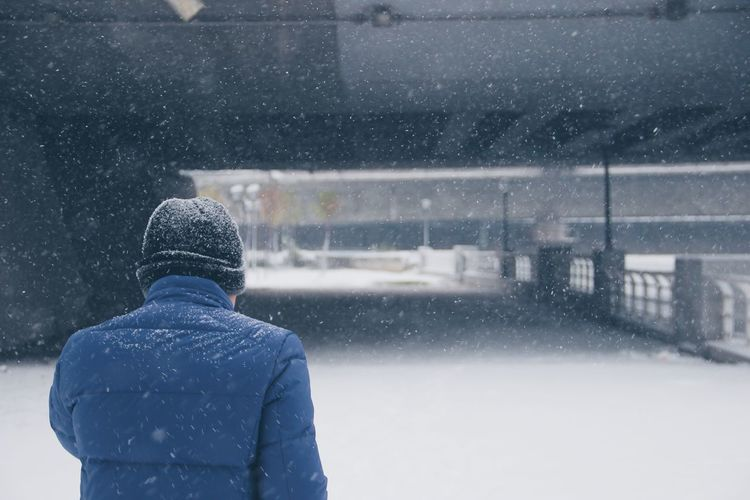 Rear view of man on snow covered road in city