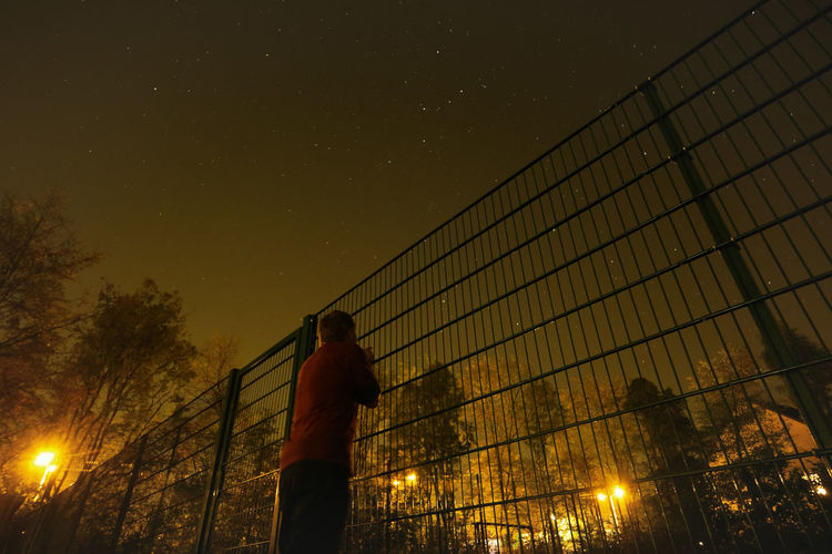 Man Looking Through Fence Against Trees